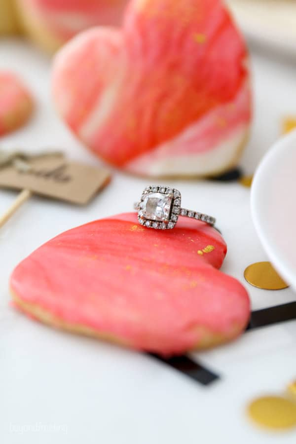 A gorgeous, princess cut diamond engagement ring leaning up against a heart shaped cookie dusted with gold edible glitter