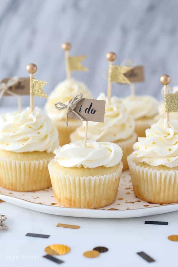 These engagement themed cupcakes are super cute decorated with a buttercream rose and a little gold flag cupcake topper