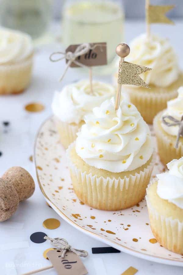 These engagement themed cupcakes are super cute decorated with a beautiful buttercream swirl with gold heart shaped sprinkles a a gold flag cupcake topped