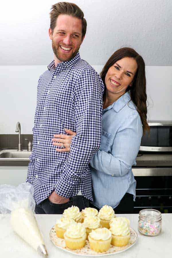 These cute husband and wife engagement photos in their home kitchen featuring some engagement themed cupcakes