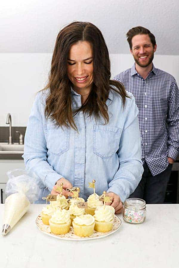 Husband and wife engagement photos in their home kitchen with a plate of cupcakes, a piping bag and sprinkles. The bride is garnishing the cupcakes and the groom is blurred out in the background smiling.
