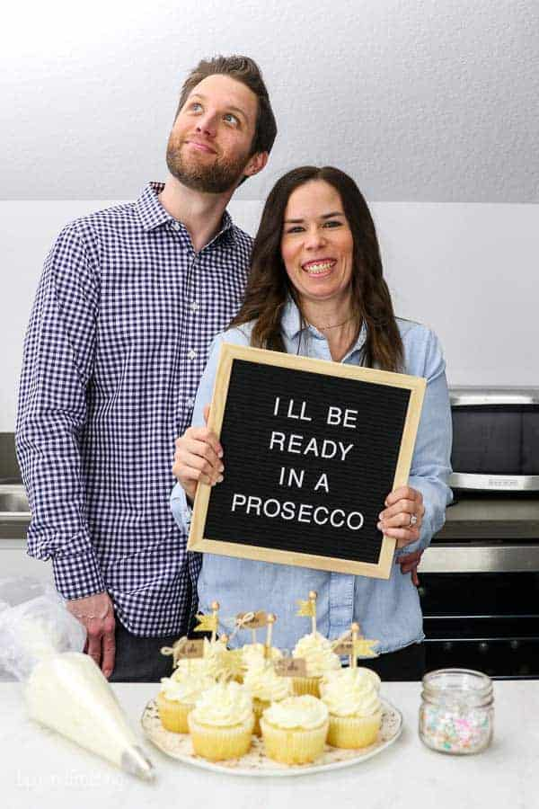 "Husband and wife engagement photos in their home kitchen with a plate of cupcakes, a piping bag and sprinkles. The bride is holding a letterboard sign that says ""I'll be ready in a prosecco"""