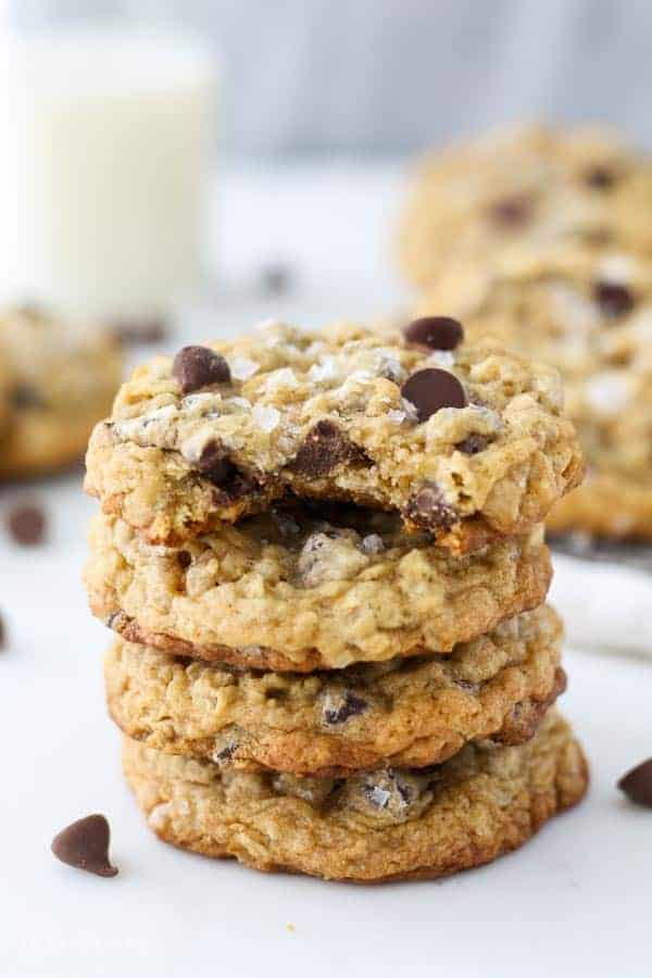 A big stack of chocolate chip oatmeal cookies, the cookie on top has a big bite taken out of it