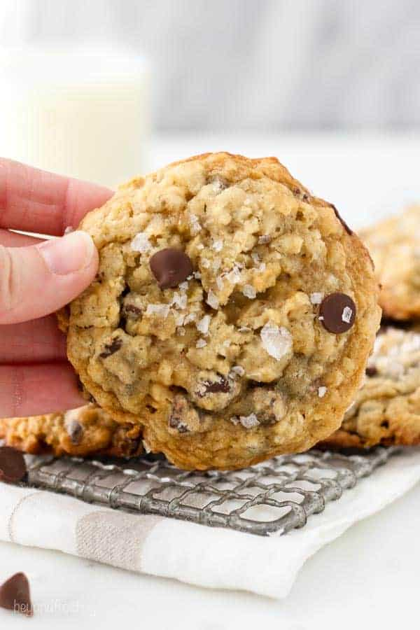 A hand is holding an oatmeal chocolate chip cookie showing the top of the cookie which has large flakes of sea salt on top