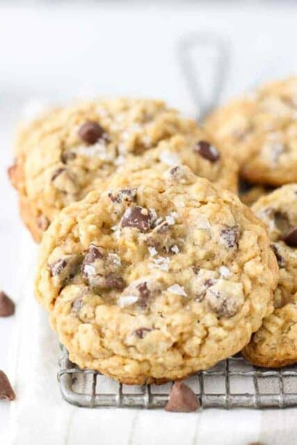 A close up of a droolworth oatmeal chocolate chip cookie with large flakes of sea salt on top. The cookie is sitting on a wire rack