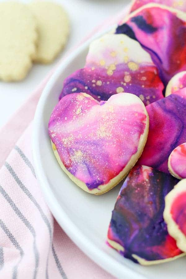 A beautiful mini heart shaped sugar cookie with marble icing and gold pearl dust decorated in Valentine's day colors
