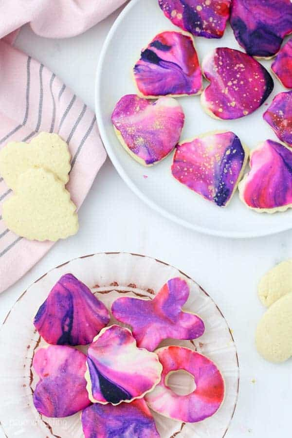 An overhead shot of galaxy swirled sugar cookies, also known as marble swirled icing. The cookies are laying on pink and white plates and decorated for valentines day. Some of the cookies have gold accents.