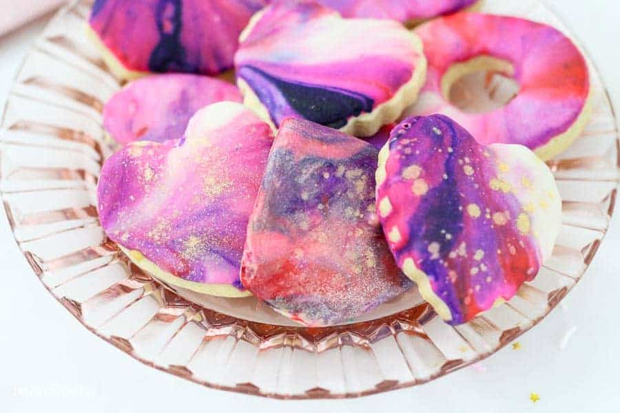 These cookies are decorated with galaxy icing which is swirled with white, pink, red and purple icing. They are dusted with a gold pearl dust.