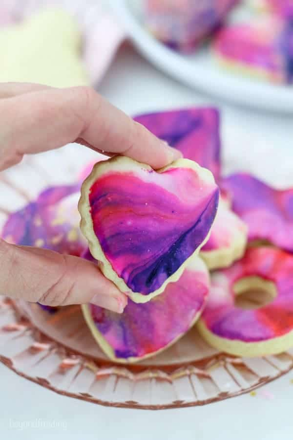 A hand is holding a mini heart shaped cookie with ruffled edges. The cookie is decorated with galaxy icing which is swirled with white, pink, red and purple icing.