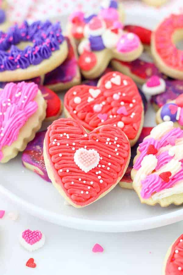 A red buttercream frosted heart shaped cookie with a mini heart sprinkle on it.