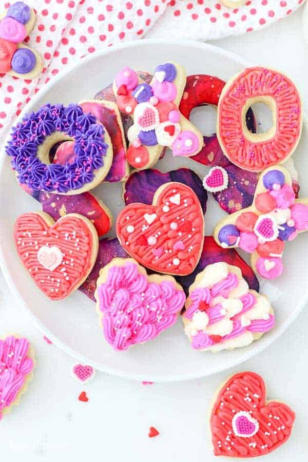 A white plate full of mini decorated sugar cookies with a valentine's day theme including heart shaped cookies, XO cookies and diamond shaped cookies all decorated with colorful buttercream frosting