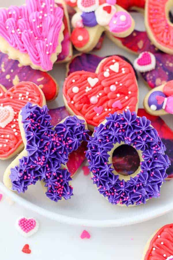 Mini X and O decorated sugar cookies are Valentine's day themed. These are frosted with a bright purple buttercream and garnished with hot pink sprinkles