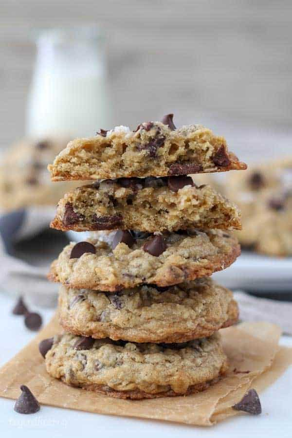 A stack of 3 oatmeal chocolate chip cookies, and a 4th cookie on top is broken in half showing the inside layers of the cookies. There's a glass of milk blurred out in the background
