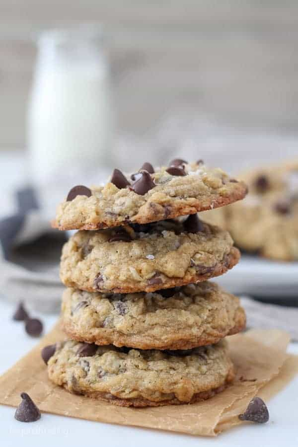 A stack of 4 oatmeal chocolate chip cookies with a glass of milk blurred out in the background