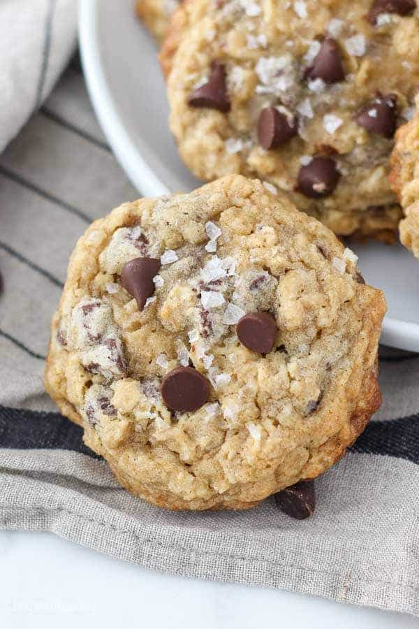 A big salty oatmeal chocolate chip cookie leaning up against a white plate