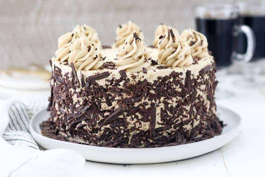 A 3 layer chocolate cake covered in a mocha buttercream and chocolate shavings sitting on a light gray rimmed plate