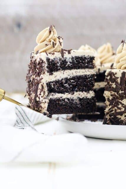 A gold serving spatula is holding a slice of 3 layer of chocolate cake with mocha buttercream and chocolate shavings.