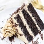 A close up of a 3 layer chocolate cake covered in a mocha buttercream is laying sideways on a white rimmed plate with chocolate shavings, there's two gold forks in the background.