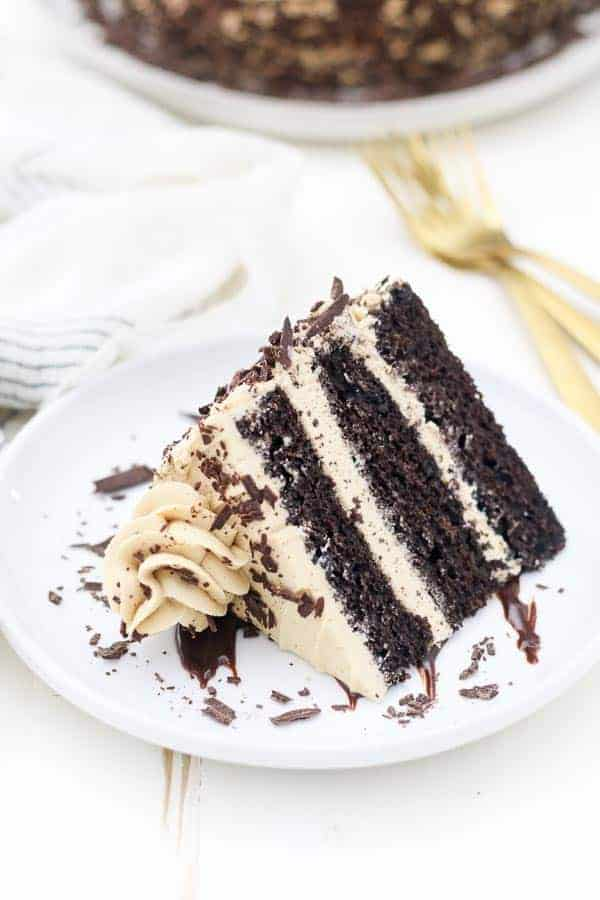 A 3 layer chocolate cake covered in a mocha buttercream is laying sideways on a white rimmed plate with chocolate shavings, there's two gold forks in the background and a crumpled up napkin