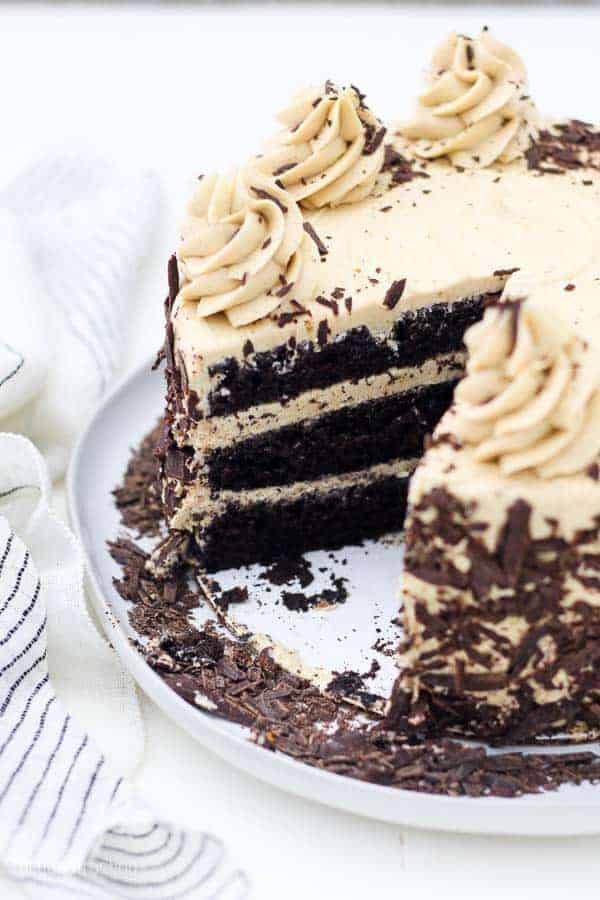 A large 3 layer chocolate cake is covered with a coffee buttercream. The cake has a large slice taken out of it, and the cake is covered with chocolate shavings.