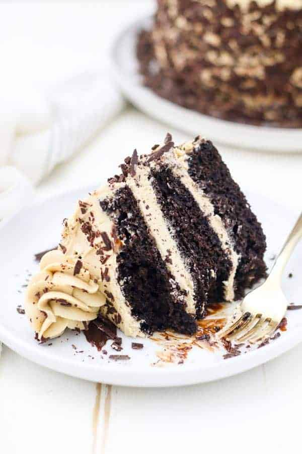 A slice of 3 layer chocolate cake with a coffee buttercream laying sideways on a plate has a few bites taken out of it and a gold fork leaning up against the side.