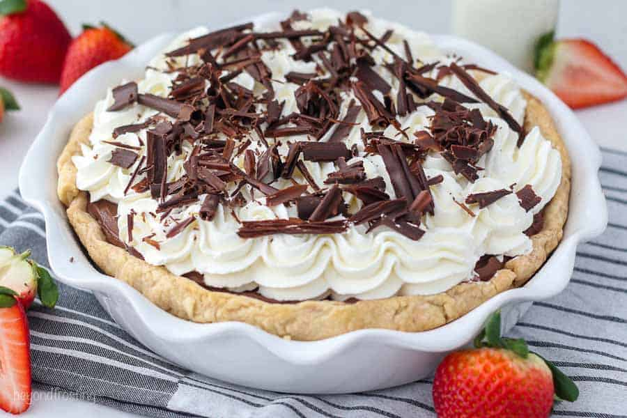 A white ruffled edge pie plate is filled with a chocolate pudding pie., whipped cream and chocolate shaving with some diced strawberries