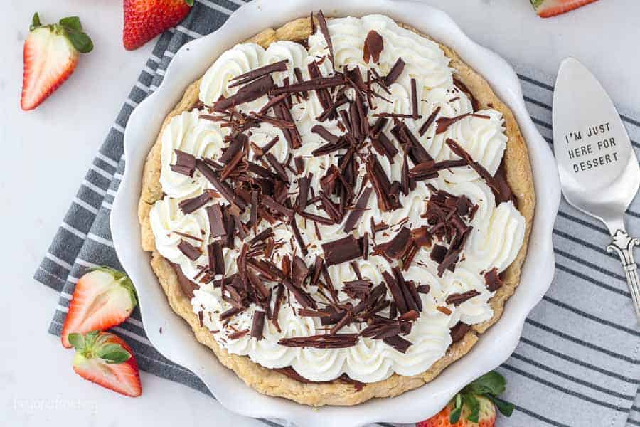 "An overhead shot of a whole chocolate cream pie showing the whipped cream topping and chocolate shavings. There's a silver pie servers that says ""I'm just here for dessert"""
