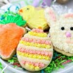 Adorable Easter cookies sitting on paper grass. There's an Easter egg, a bunny face, a carrot and a chick. The cookies are decorated with pink and yellow buttercream and sprinkles.