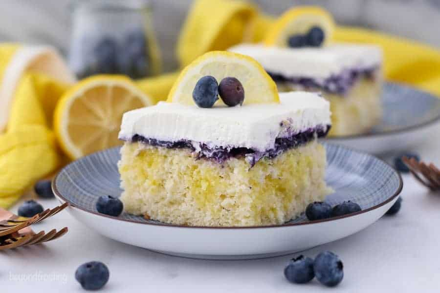 A wide shot of a A close up shot of a slice of lemon blueberry cake, showing the lemon pudding filling, the blueberry topping and the whipped cream is garnished with a lemon slice and a couple of blueberries. The background is blurred out with another slice of cake, a sliced lemon and a jar of blueberries.
