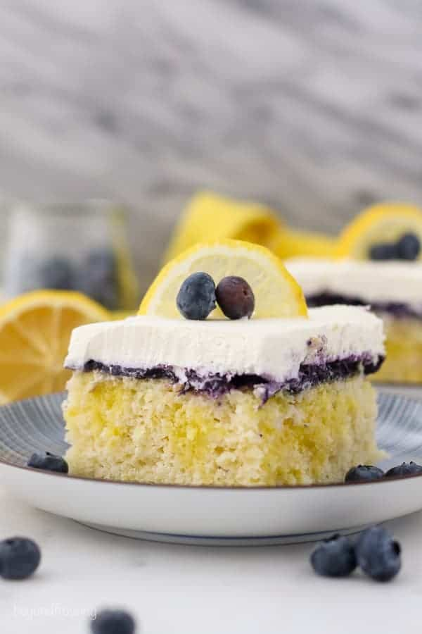 A shot of a slice of lemon blueberry cake, showing the lemon pudding filling, the blueberry topping and the whipped cream is garnished with a lemon slice and a couple of blueberries. There's a lemon and jar of blueberries blurred out in the background