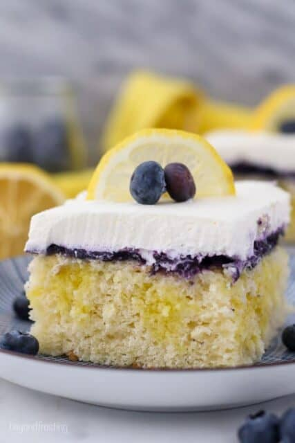 A close up shot of a slice of lemon blueberry cake, showing the lemon pudding filling, the blueberry topping and the whipped cream is garnished with a lemon slice and a couple of blueberries