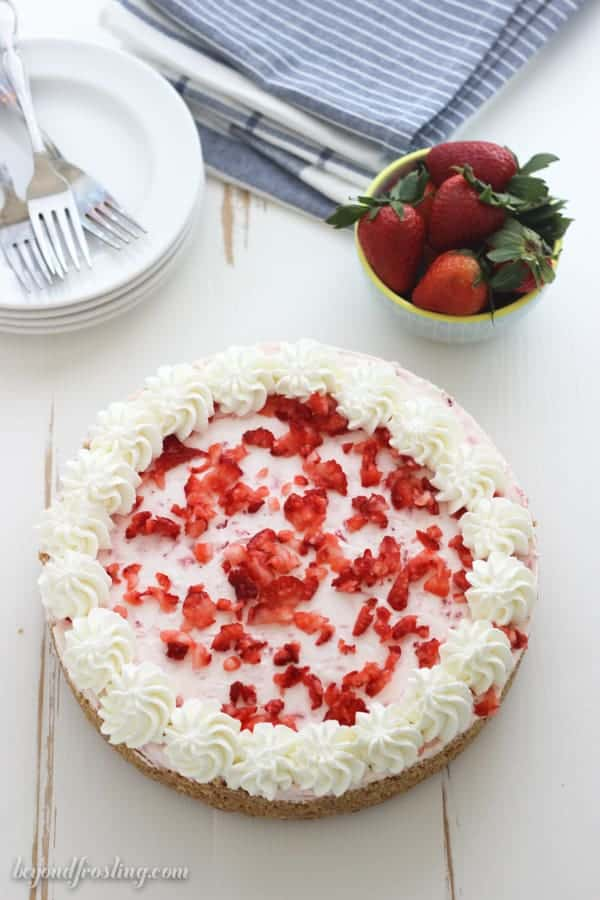 An overhead shot of a strawberry pie with a blue bowl of strawberries in it, a blue napkin in the background and a stack of white rimmed plates with 3 silver forks on top.