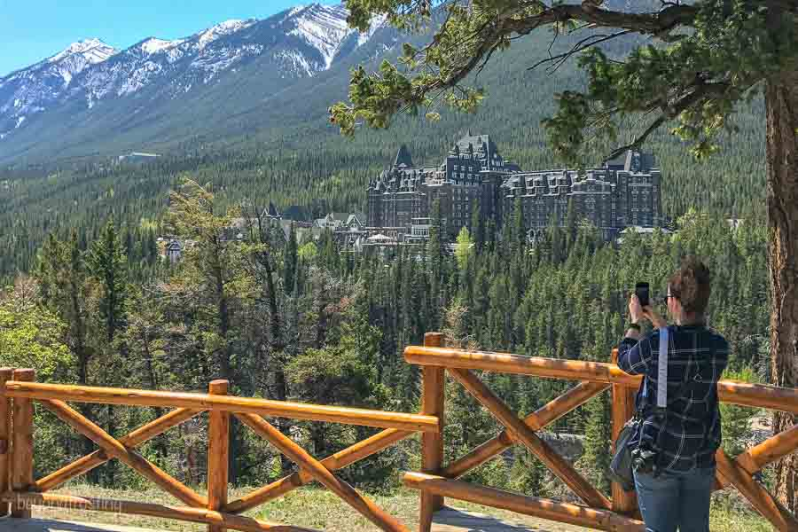 Surprise Corner in Banff National Park overlooking the Fairmont Hotel, women is taking a picture with her iphone