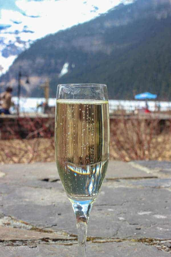 A glass of champagne with Lake Louise hiding in the background