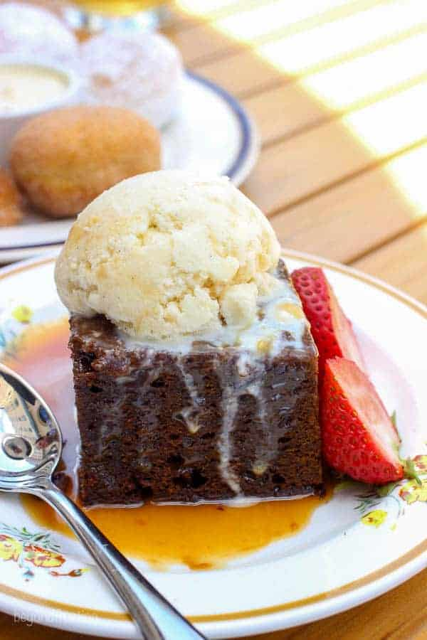 Chocolate brownie with a scoop of ice cream and two strawberries