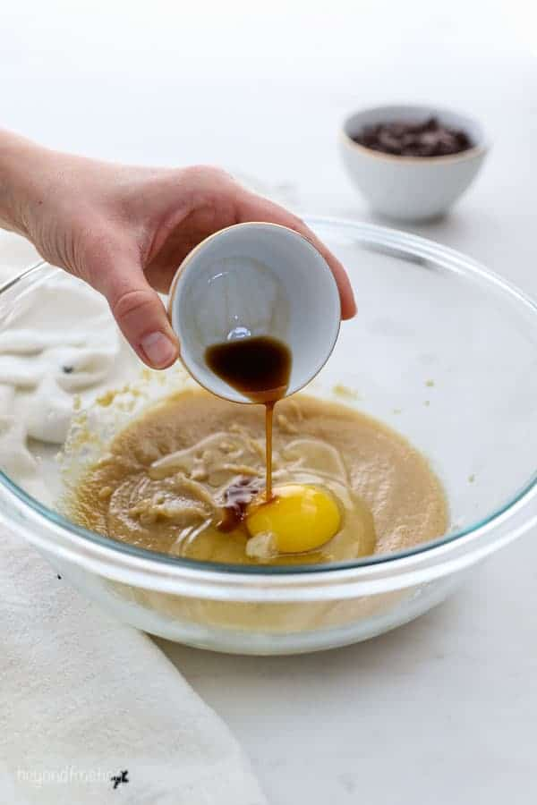 A hand is pouring some vanilla extract into a bowl of creamed butter and sugar, there's also an egg in the bowl.