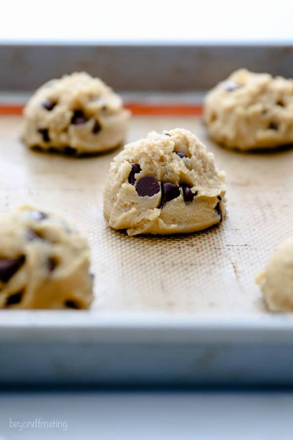 A scoop of raw cookie dough on a baking sheet