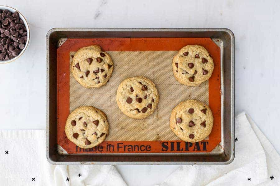 An overhead shot of a baking sheet, lined with a silicone baking mat and 5 baked chocolate chip cookies