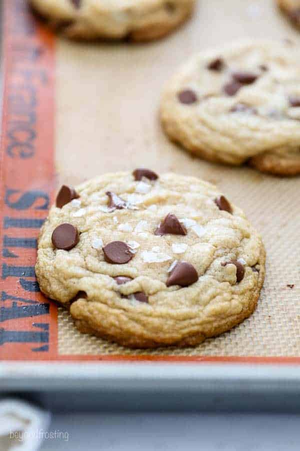 Perfectly baked chocolate chip cookies sitting on a silicone baking mat. The cookie is topped with flaky sea salt.