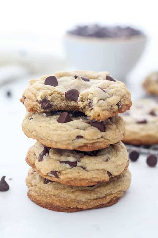 A stack of 4 chocolate chip cookies, the cookie on top had a bite taken out of it