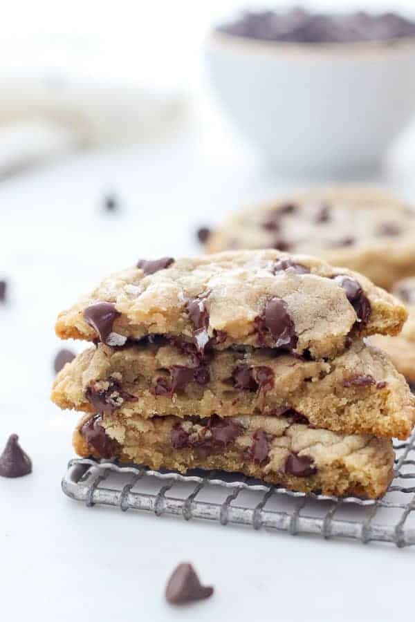 A stack of 3, half broken gooey chocolate chip cookies with chocolate chips melting from the middle