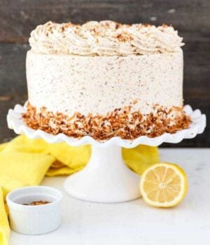 A gorgeous layer cake frosted with toasted coconut buttercream, with toasted coconut pressed into the bottom edge. It's sitting on a white ruffled cake plate, and there's a yellow napkin and sliced lemon sitting next to it.