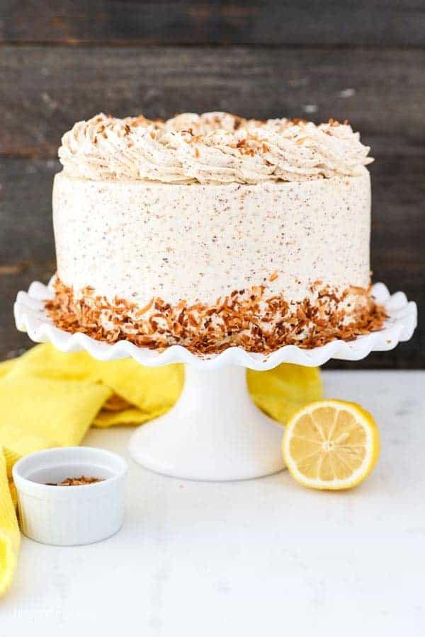 A Lemon Coconut Cake on a Cake Stand Next to Half a Lemon