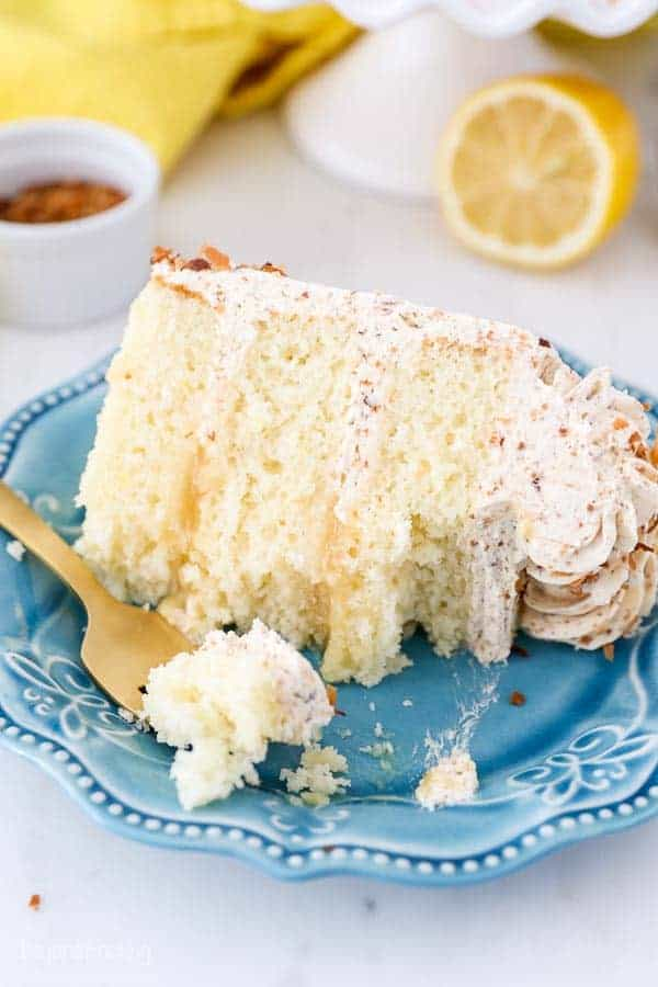 A 3 layer lemon cake with a lemon curd filling, there's several bites missing from the cake, and a big gold fork with a bite of cake on it.
