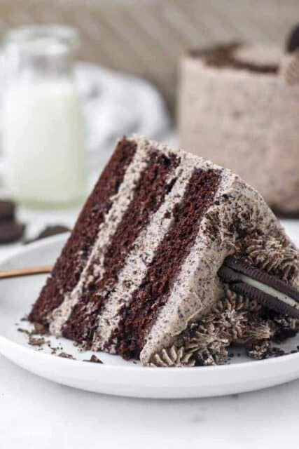A 3 layer chocolate cake with Oreo frosting laying on a large white cake plate. The top of the slice of cake has Oreo rosettes and more cookies