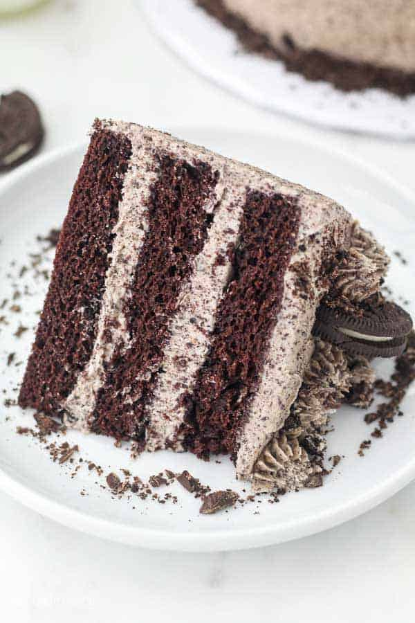 A 3 layer chocolate cake with Oreo icing on a large white cake plate sprinkled with chocolate shavings