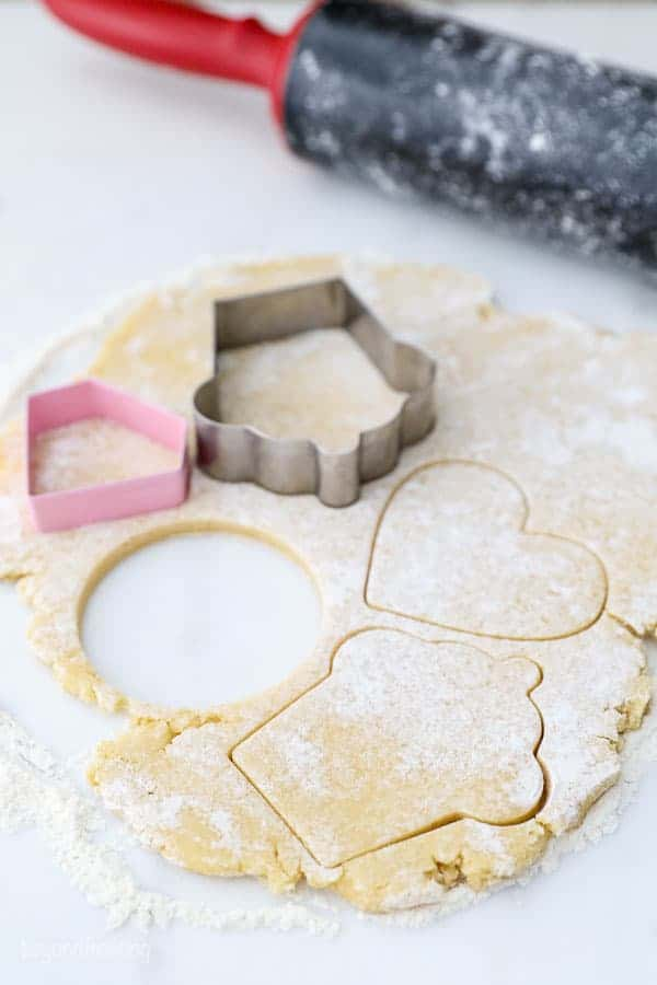 Sugar cookie dough is rolled out, with a few cookie cutters pressed into it and some of them have already been taken out