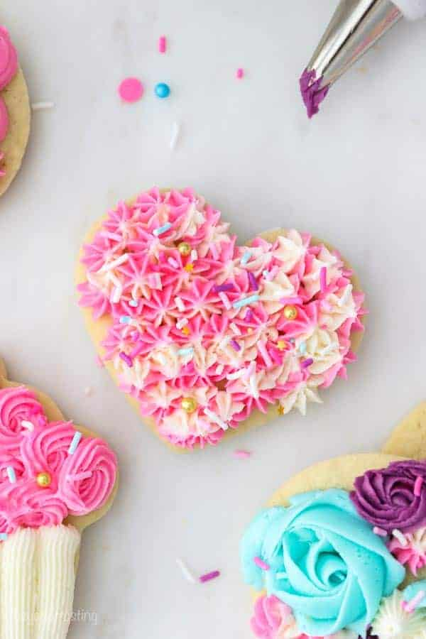 A heart shaped sugar cookie decorated with a tip 18 open star tip is a marbled pink and white buttercream and garnished with sprinkles