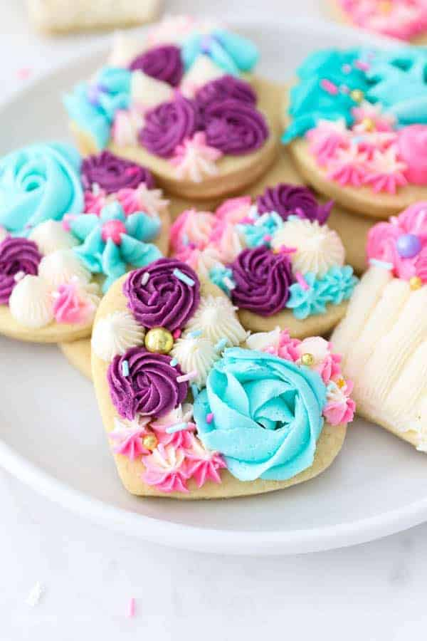 A gorgeous plate of sugar cookies decorated with vanilla buttercream