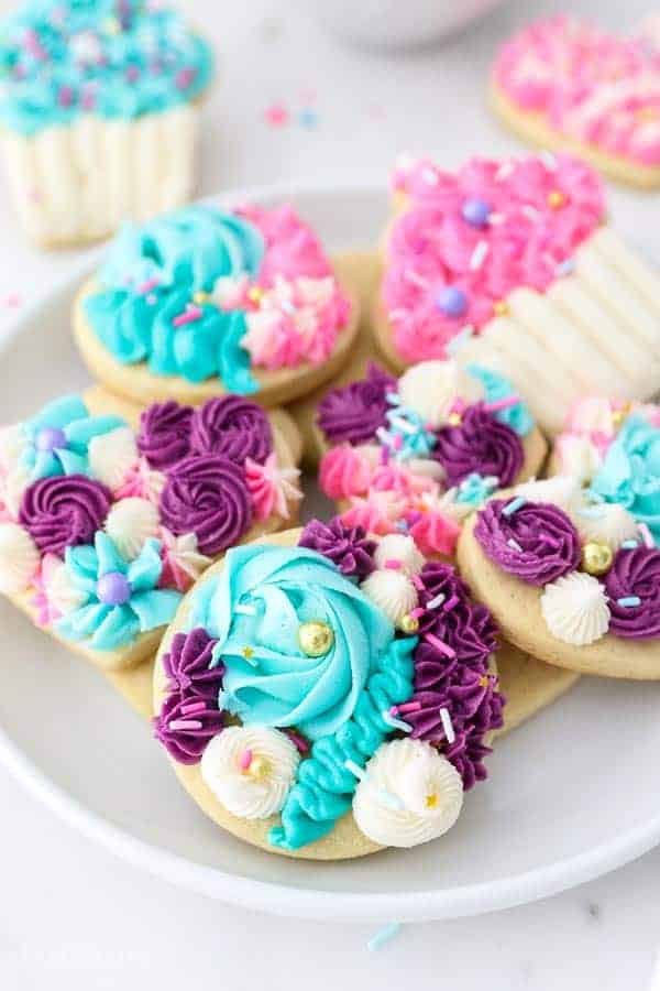 A plate full of gorgeous sugar cookies decorated with buttercream in purple, teals, white and pink frosting.